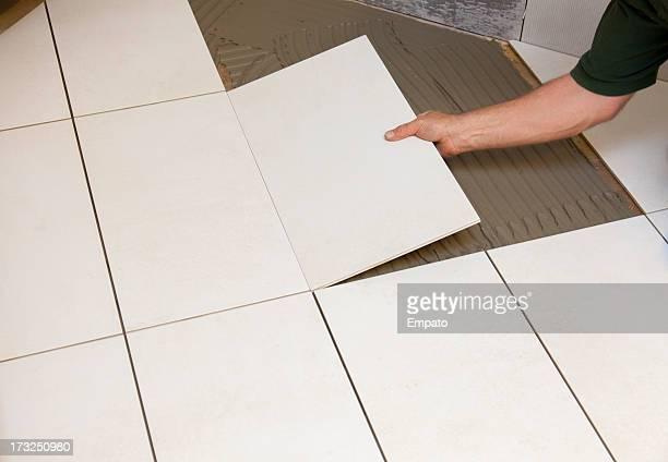 Tile fixer laying ceramic floor tiles.