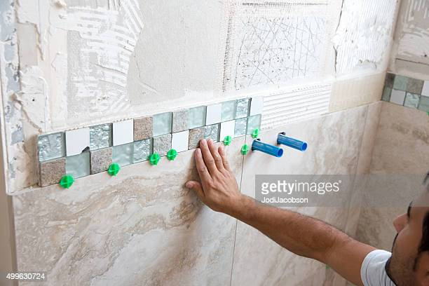 Tile series:Tile border being installed on shower wall in home