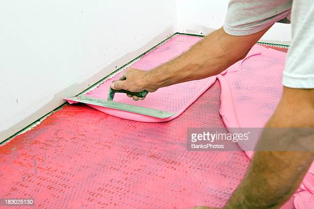 Tile Setter Spreading Waterproof Membrane on Laundry Room Floor