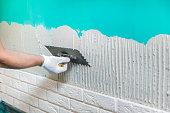 tiler applying tile adhesive on the wall