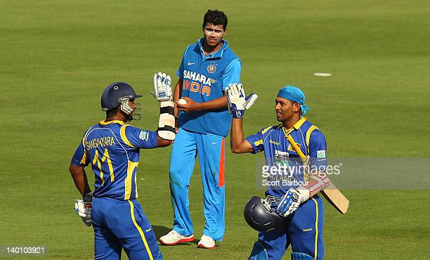 Tillakaratne Dilshan of Sri Lanka is congratulated by Kumar Sangakkara of Sri Lanka after reaching his century as Ravindra Jadeja of India looks on...