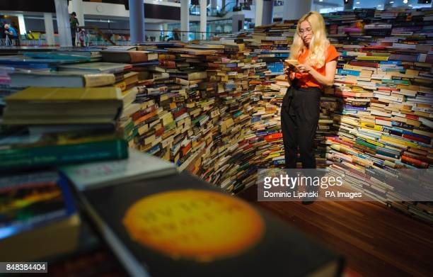Tilly Shiner reads a book inside the 'aMAZEme' installation a maze constructed of 250000 books by Brazilian artists Marcos Saboya and Gualter Pupo at...