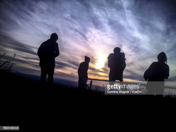 Tilt Image Of Silhouette Friends Standing At Beach Against Sky During Sunset