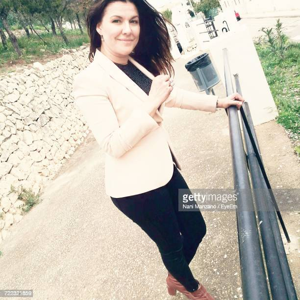 Tilt Shot Of Beautiful Woman Standing By Railing On Footpath
