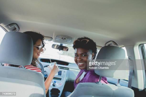 Tilt shot of happy female friends sitting in car