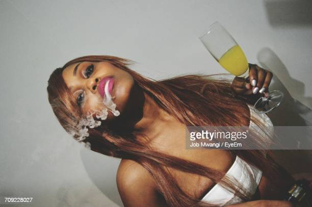 Tilt Shot Of Seductive Woman Holding Drink While Smoking Against Wall
