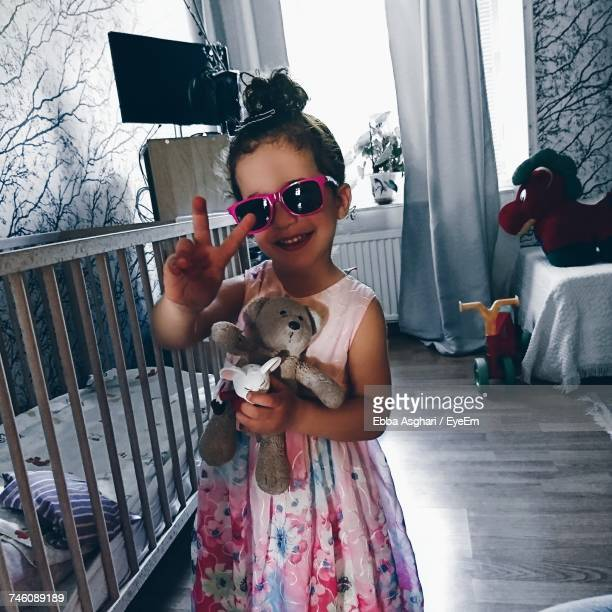 Tilt Shot Of Smiling Girl Holding Teddy Bear Showing Peace Sign While Standing By Crib At Home