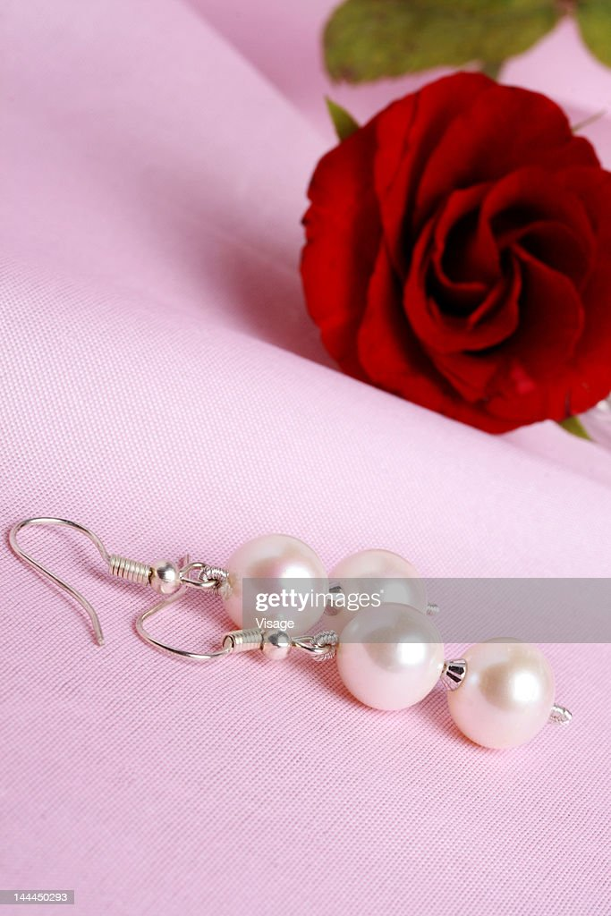 Tilted view of ear rings and a rose