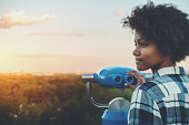 Tilt-shift portrait of meditative young black female with afro curly hair standing in high observation point and holding blue binocular with copy space zone for text, logo or your advertising, sunset