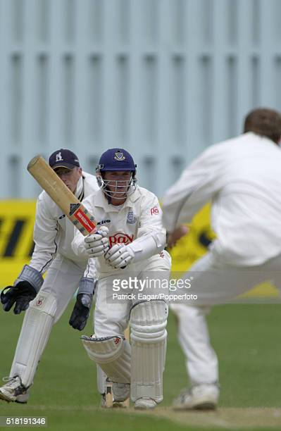 Tim Ambrose of Sussex straight drives a delivery from Neil Smith of Warwickshire who deflects the ball onto the stumps running out Tony Cottey of...