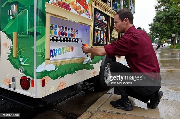 Tim Bailey pours flavored syrup on a shaved ice at the Kona Shaved Ice truck in Denver Colorado on August 24 2016 Kona serves shaved ice and ice cream