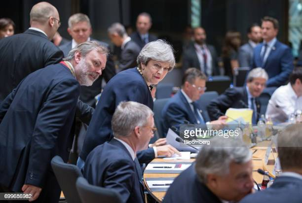 Tim Barrow UK permanent representative to the European Union left and Theresa May UK prime minister center arrive for the start of round table talks...