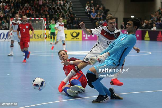 Tim Baumer of Germany and Stuart Cook and Thomas Dennis of England compete for the ball during the Futsal International Friendly match between...