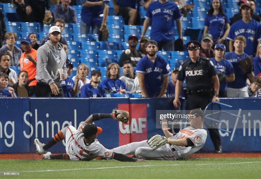 Tim Beckham #1 of the Baltimore Orioles and Trey Mancini #16 slide in pursuit of a foul pop up that drops before they can get to it in the sixth inning during MLB game action against the Toronto Blue Jays at Rogers Centre on September 12, 2017 in Toronto, Canada.