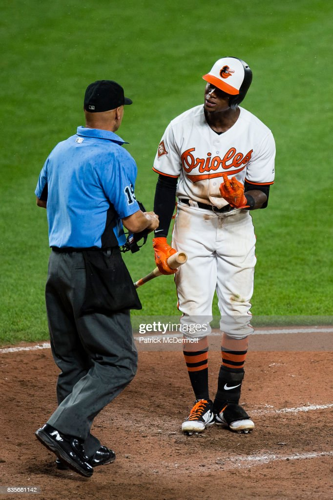 Tim Beckham #1 of the Baltimore Orioles argues with home plate umpire Vic Carapazza #19 after he stuck out looking to end the seventh inning during a game against the Los Angeles Angels of Anaheim at Oriole Park at Camden Yards on August 19, 2017 in Baltimore, Maryland.