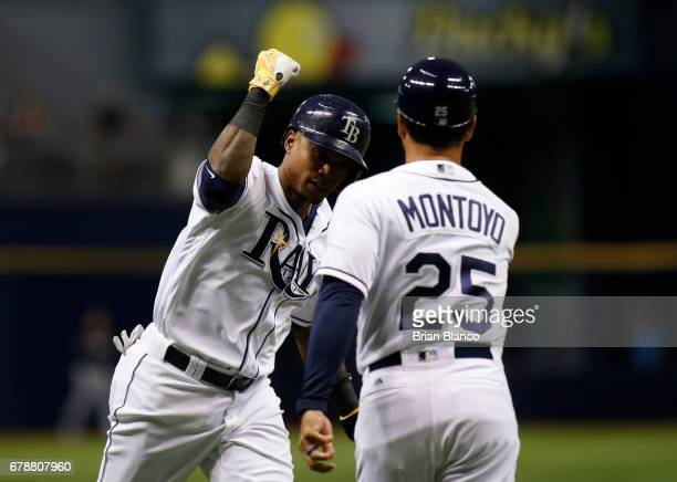 Tim Beckham of the Tampa Bay Rays celebrates his tworun home run with third base coach Charlie Montoyo during the second inning of a game against the...