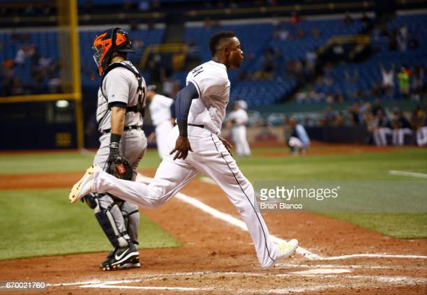 Tim Beckham of the Tampa Bay Rays crosses home plate ahead the throw to catcher Alex Avila of the Detroit Tigers to score on a double by Kevin...