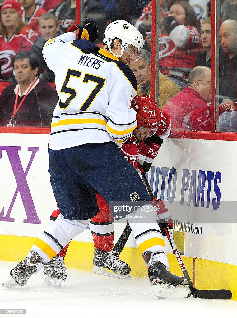 Tim Brent #37 of the Carolina Hurricanes battles for the puck along the boards with Tyler Myers #57 of the Buffalo Sabres during play at PNC Arena on January 24, 2013 in Raleigh, North Carolina.