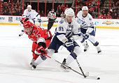 Tim Brent of the Carolina Hurricanes reaches for the puck around Steven Stamkos of the Tampa Bay Lightning during a NHL game on November 1 2011 at...