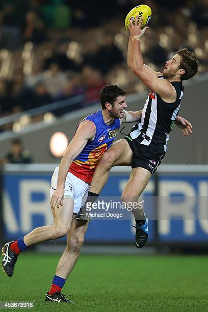 Tim Broomhead of the Magpies marks the ball against Darcy Gardiner of the Lions during the round 21 AFL match between the Collingwood Magpies and the...