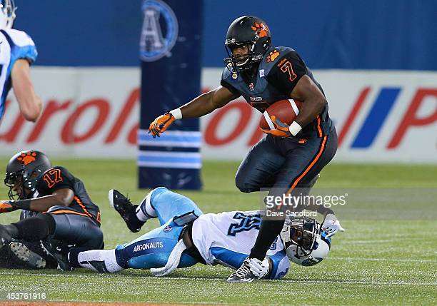 Tim Brown of the BC Lions avoids a tackle by Vincent Agnew of the Toronto Argonauts during their game at Rogers Centre on August 17 2014 in Toronto...