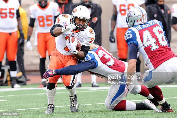 Tim Brown of the BC Lions is tackled with the ball by James Tuck of the Montreal Alouettes during the CFL Eastern Division SemiFinal game at Percival...