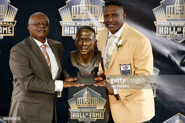 Tim Brown poses with his bust along with his brother Donald Kelly during the NFL Hall of Fame induction ceremony at Tom Benson Hall of Fame Stadium...