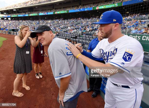 Tim Brown winner of the Sonic Slam Grand Slam $25000 prize has his Kansas City Royals Cam Gallagher jersey signed by Gallagher during a pregame...