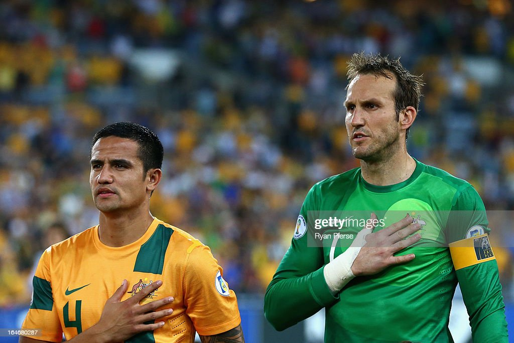 Tim Cahill and Mark Schwarzer of the Socceroos look on during the national anthem during the FIFA 2014 World Cup Qualifier match between the Australian Socceroos and Oman at ANZ Stadium on March 26, 2013 in Sydney, Australia.