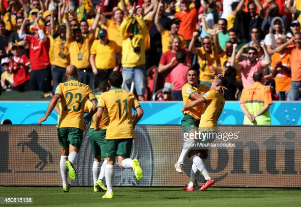Tim Cahill of Australia celebrates with teammates after scoring his team's first goal during the 2014 FIFA World Cup Brazil Group B match between...