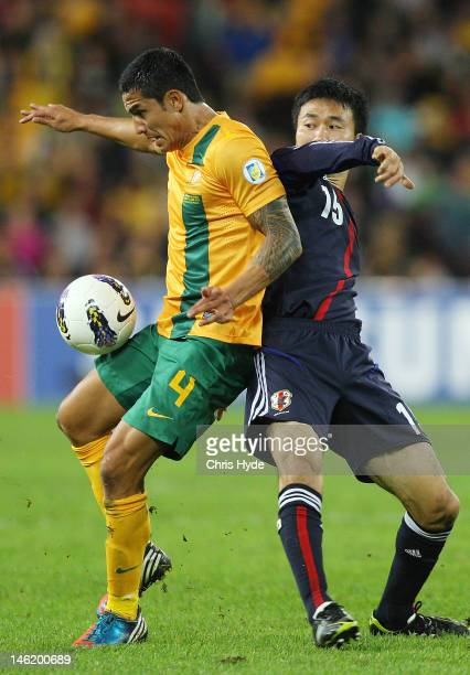 Tim Cahill of Australia controls the ball from Yasuyuki Konno of Japan during the FIFA World Cup Asian Qualifier match between the Australian...