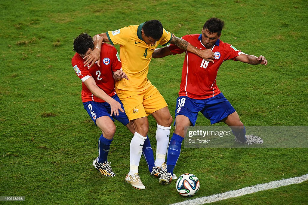 <a gi-track='captionPersonalityLinkClicked' href=/galleries/search?phrase=Tim+Cahill+-+Soccer+Player&family=editorial&specificpeople=209085 ng-click='$event.stopPropagation()'>Tim Cahill</a> of Australia fights off challenges by <a gi-track='captionPersonalityLinkClicked' href=/galleries/search?phrase=Eugenio+Mena&family=editorial&specificpeople=5900221 ng-click='$event.stopPropagation()'>Eugenio Mena</a> (L) and <a gi-track='captionPersonalityLinkClicked' href=/galleries/search?phrase=Gonzalo+Jara&family=editorial&specificpeople=860125 ng-click='$event.stopPropagation()'>Gonzalo Jara</a> of Chile during the 2014 FIFA World Cup Brazil Group B match between Chile and Australia at Arena Pantanal on June 13, 2014 in Cuiaba, Brazil.