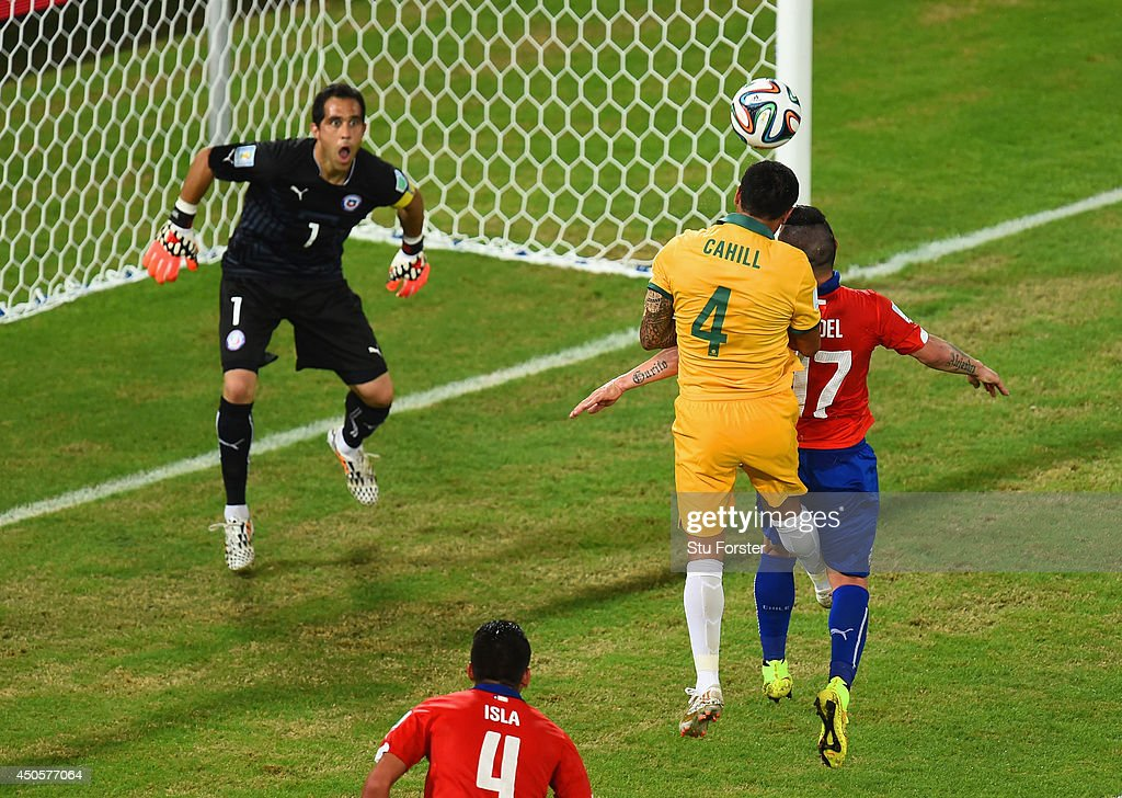 Tim Cahill of Australia goes up for a header against Gary Medel of Chile and scores a goal past goalkeeper Claudio Bravo during the 2014 FIFA World Cup Brazil Group B match between Chile and Australia at Arena Pantanal on June 13, 2014 in Cuiaba, Brazil.