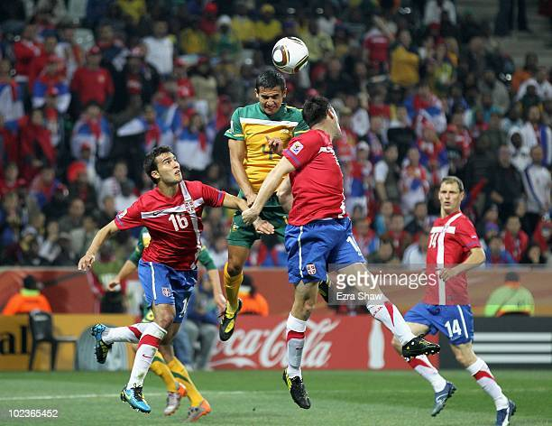 Tim Cahill of Australia goes up for the ball against Ivan Obradovic and Aleksandar Lukovic of Serbia during the 2010 FIFA World Cup South Africa...
