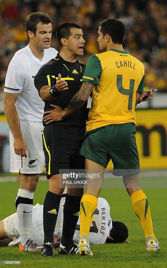 Tim Cahill of Australia is reprimaned by the referee before he receives a yellow card after a clash with Leo Bertos of New Zealand (floor) during their friendly international football match in Melbourne on May 24, 2010. Australia won the match 2-1. RESTRICTED