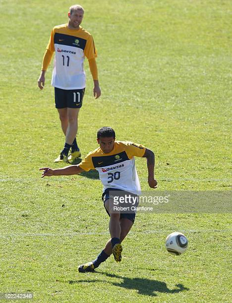 Tim Cahill of Australia kicks the ball as Scott Chipperfield looks on during an Australian Socceroos training session at Ruimsig Stadium on June 20...