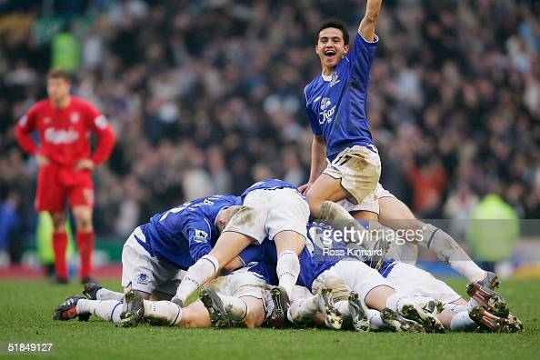 Tim Cahill of Everton celebrates as the Everton tean pile on top of goal scorer Lee Carsley during the Barclays Premiership match between Everton and...