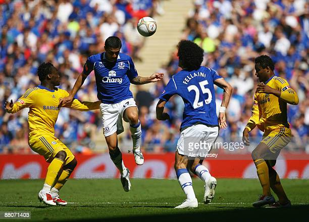 Tim Cahill of Everton wins a header as Michael Essien and John Obi Mikel of Chelsea look on with Marouane Fellaini of Everton during the FA Cup...