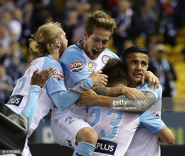 Tim Cahill of Melbourne City celebrates with team mates after scoring a goal during the round two ALeague match between Melbourne Victory and...