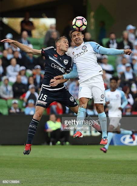 Tim Cahill of Melbourne Cityheads the ball ahead of Alan Baro of the Victory during the round 11 ALeague match between Melbourne City FC and...