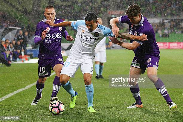 Tim Cahill of the City compete for the ball against Marc Warren of the Glory and Alex Grant during the round three ALeague match between Melbourne...