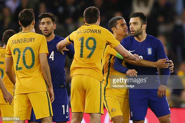 Tim Cahill of the Socceroos holds back Giorgios Tzavellas of Greece from Trent Sainsbury of the Socceroos after a contest during the International...