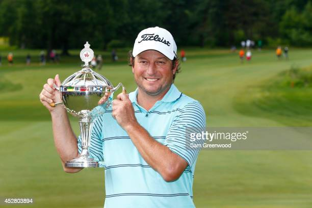Tim Clark of South Africa holds the trophy after winning the RBC Canadian Open at the Royal Montreal Golf Club on July 27 2014 in Montreal Quebec...