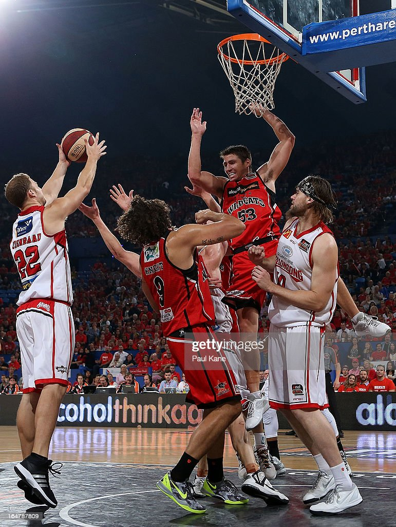 Tim Coenraad of the Hawks rebounds after a failed tip in by <a gi-track='captionPersonalityLinkClicked' href=/galleries/search?phrase=Damian+Martin+-+Basketball+Player&family=editorial&specificpeople=13687064 ng-click='$event.stopPropagation()'>Damian Martin</a> of the Wildcats during game one of the NBL Semi Final Series between the Perth Wildcats and the Wollongong Hawks at Perth Arena on March 28, 2013 in Perth, Australia.