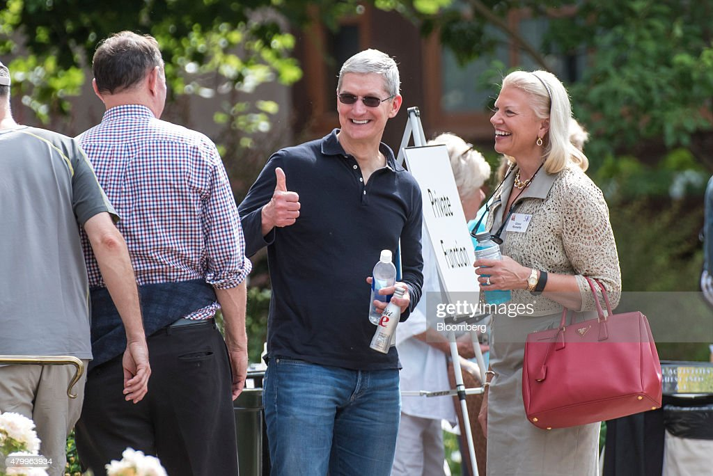Tim Cook chief executive officer of Apple Inc center gestures to Donald Graham former chairman and chief executive officer of The Washington Post Co...