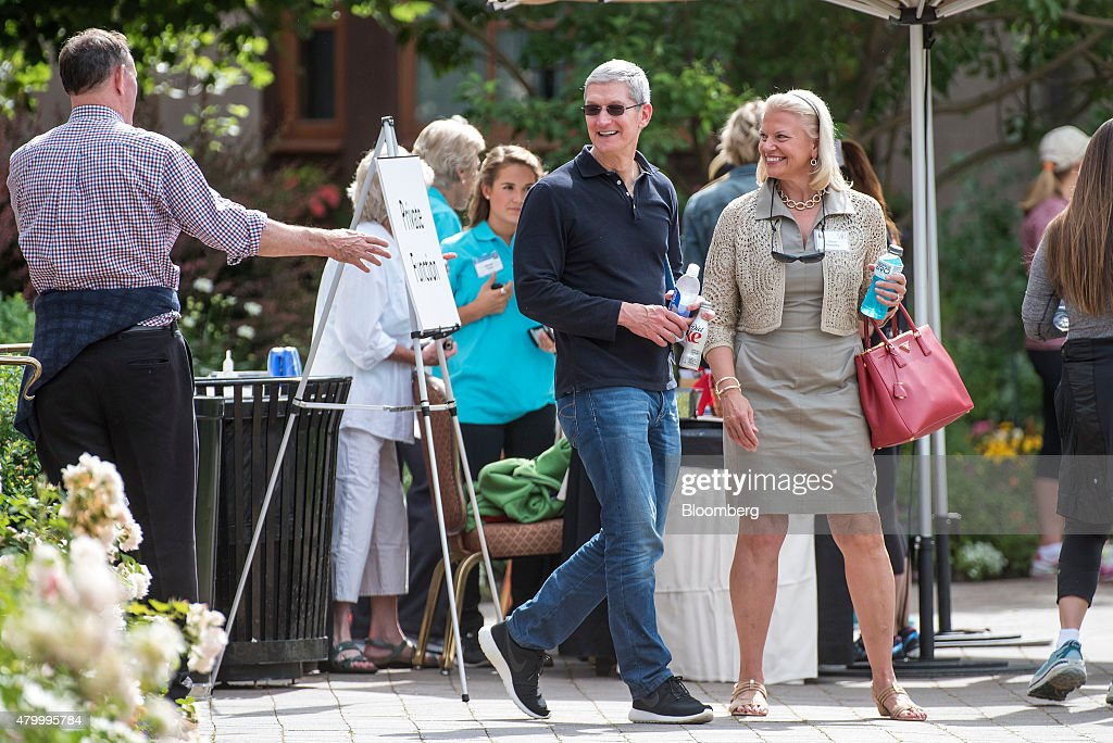 Tim Cook chief executive officer of Apple Inc center smiles as he walks away from Donald Graham former chairman and chief executive officer of The...