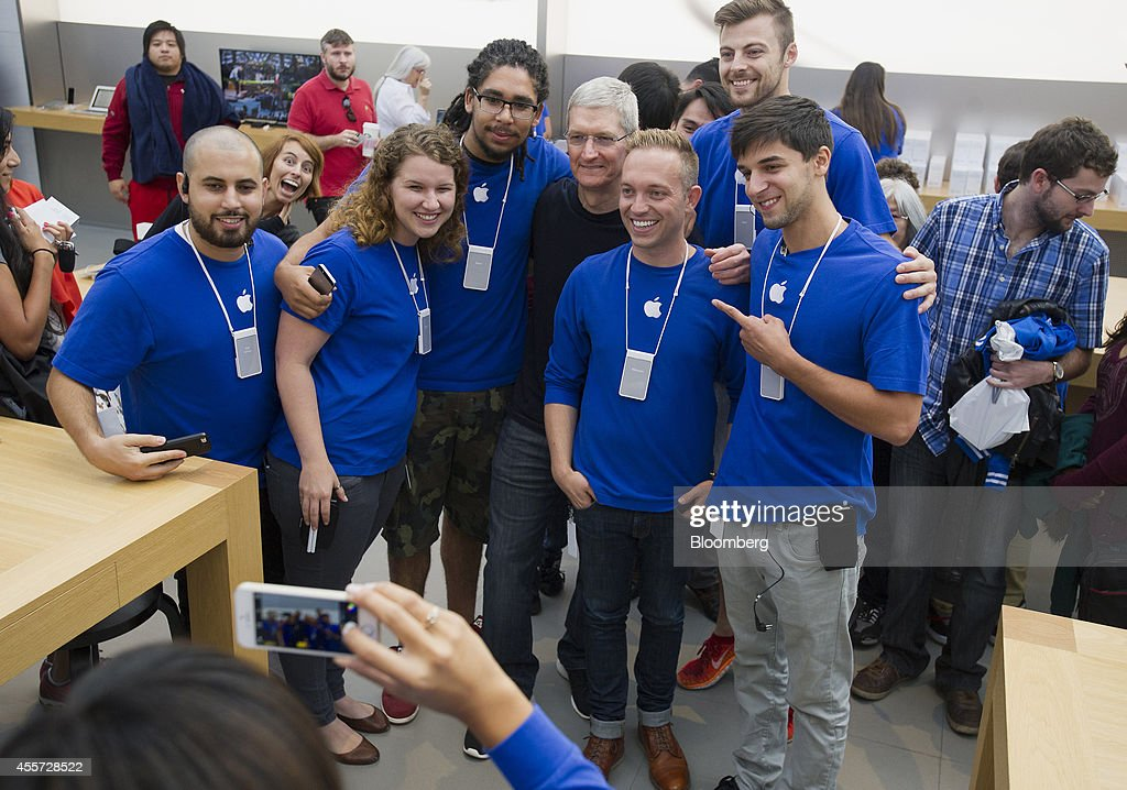 Tim Cook, chief executive officer of Apple Inc., center, stands for a photograph with employees during the sales launch for the iPhone 6 and iPhone 6 Plus at the Apple Inc. store in Palo Alto, California, U.S., on Friday, Sept. 19, 2014. Apple Inc.'s stores attracted long lines of shoppers for the debut of the latest iPhones, indicating healthy demand for the bigger-screen smartphones. The larger iPhone 6 Plus is already selling out at some stores across the U.S. Photographer: David Paul Morris/Bloomberg via Getty Images