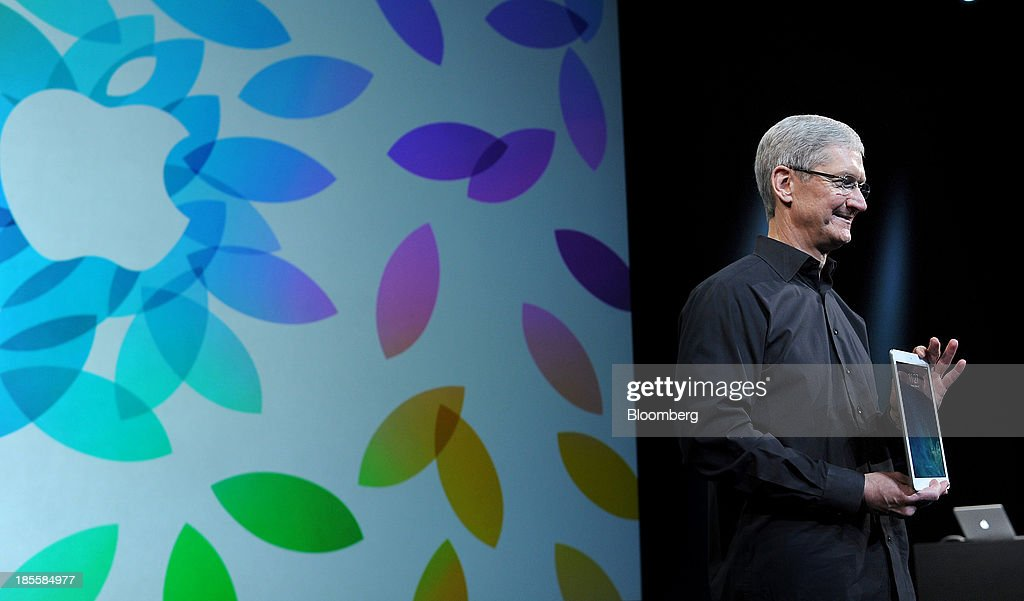 Tim Cook, chief executive officer of Apple Inc., displays the iPad Air for a photograph during a press event at the Yerba Buena Center in San Francisco, California, U.S., on Tuesday, Oct. 22, 2013. Apple Inc. introduced new iPads in time for holiday shoppers, as it battles to stay ahead of rivals in the increasingly crowded market for tablet computers. Photographer: Noah Berger/Bloomberg via Getty Images