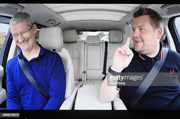 Tim Cook chief executive officer of Apple Inc left is seen on screen smiling in a car with comedian James Corden during an event in San Francisco...
