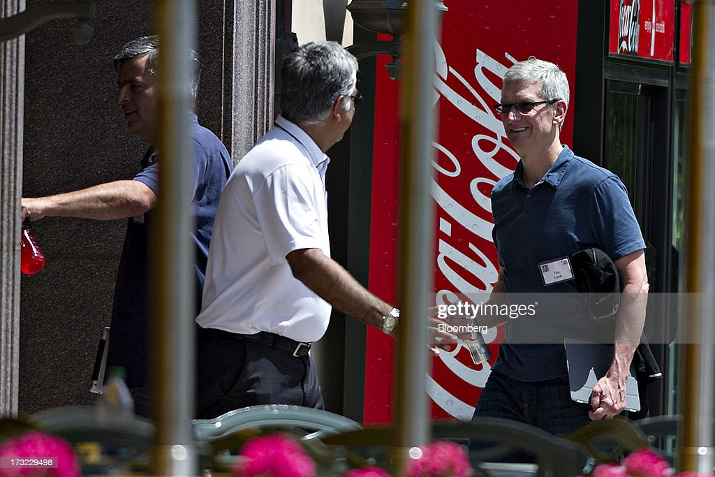 Tim Cook chief executive officer of Apple Inc right follows Eddy Cue senior vice president of internet software and services at Apple Inc left as...